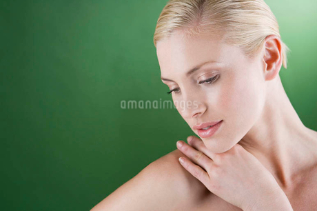 A portrait of a young blonde woman with her hand on her shoulderの写真素材 [FYI02121826]