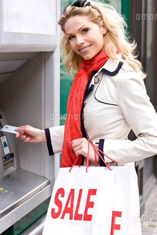 A mid adult woman using a cash machine, carrying sale bagsの写真素材 [FYI02121831]
