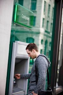A young man using a cash machineの写真素材 [FYI02121860]