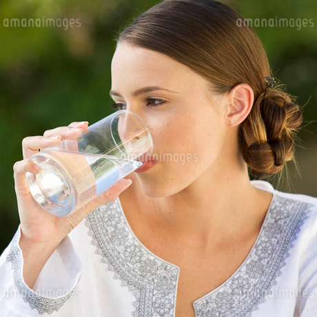 A young woman drinking a glass of waterの写真素材 [FYI02121862]
