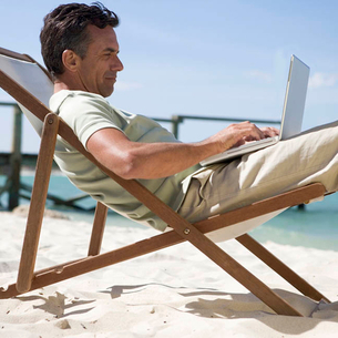 A mature man sitting in a deck chair using a laptopの写真素材 [FYI02121863]