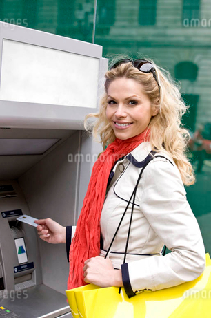 A mid adult woman using a cash machine, looking at cameraの写真素材 [FYI02121865]