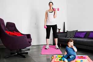 A young mother exercising at home whilst her baby son plays on the floorの写真素材 [FYI02121868]