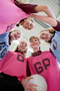 Portrait smiling high school students in huddle with netballの写真素材 [FYI02121873]