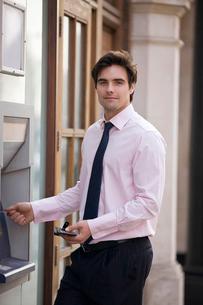A businessman using a cash machineの写真素材 [FYI02121876]