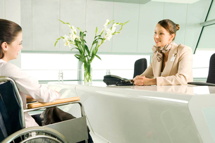 A receptionist greeting a woman in a wheelchairの写真素材 [FYI02121878]