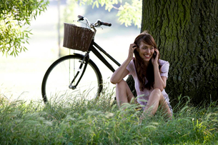 A young woman sitting under a tree talking on a mobile phoneの写真素材 [FYI02121881]