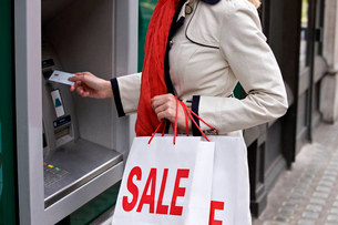 A woman using a cash machine, carrying sale bags, close-upの写真素材 [FYI02121897]