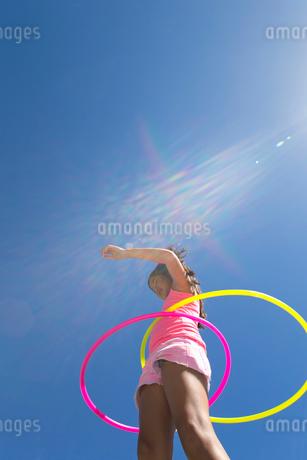 Girl spinning two plastic hoopsの写真素材 [FYI02121931]