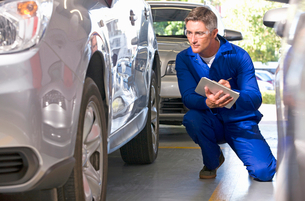 Mechanic inspecting damaged vehicleの写真素材 [FYI02121944]