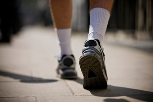 A close-up of a young man jogging in trainers, rear viewの写真素材 [FYI02121954]