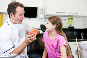 A male dentist explaining healthy eating to a young girl patientの写真素材 [FYI02121968]