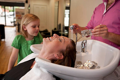 A girl watching her mum have foils removed from her hair in a hairdressing salonの写真素材 [FYI02121996]