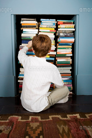 boy choosing book from bookshelfの写真素材 [FYI02122004]