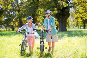 Senior couple, pushing mountain bikes, in treelined fieldの写真素材 [FYI02122016]