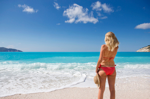 woman, looking out to sea and holding sun hat, standing on sunny beachの写真素材 [FYI02122056]