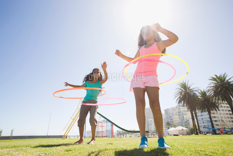 Girls spinning plastic hoops at playgroundの写真素材 [FYI02122061]