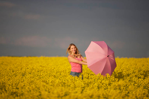A young woman standing in a rape seed field holding a pink umbrellaの写真素材 [FYI02122062]