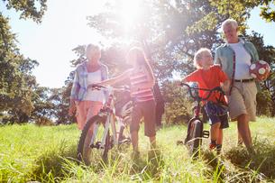 Grandparents and grandchildren pushing mountain bikes in rural fieldの写真素材 [FYI02122071]