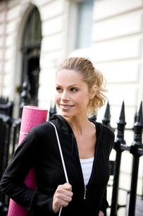 A mid adult woman carrying a yoga mat, walkingの写真素材 [FYI02122073]