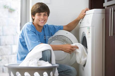 A young boy loading the washing machineの写真素材 [FYI02122079]