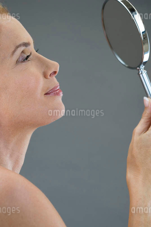 A middle-aged woman looking at her face in the mirrorの写真素材 [FYI02122087]
