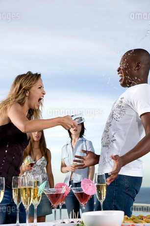 woman throwing a drink over a man at partyの写真素材 [FYI02122089]