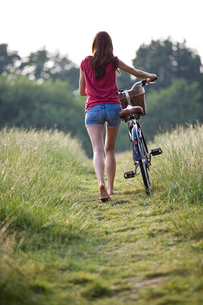 A young woman pushing a bicycle through a fieldの写真素材 [FYI02122106]