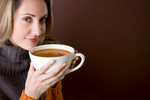 A mid adult woman holding a cup of soupの写真素材 [FYI02122164]