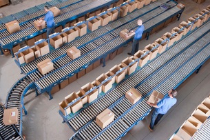 Workers packing boxes on conveyor belts in distribution warehouseの写真素材 [FYI02122172]