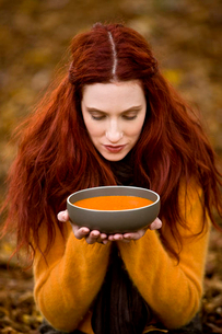 A young woman holding a bowl of soupの写真素材 [FYI02122177]