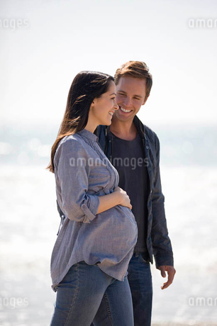 A pregnant woman and her partner walking on the beachの写真素材 [FYI02122184]