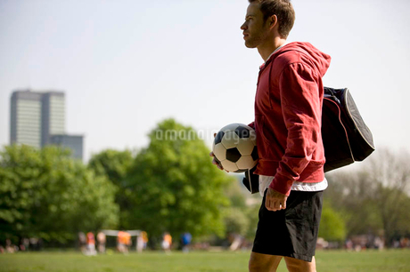 A young man standing in the park, carrying a football and a sports bagの写真素材 [FYI02122185]