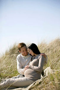 A pregnant woman and her partner sitting amongst the sand dunesの写真素材 [FYI02122191]