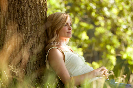 A young woman leaning against a tree, restingの写真素材 [FYI02122196]