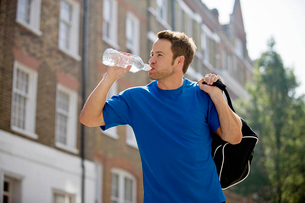A young man drinking a bottle of water, carrying a sports bag outdoorsの写真素材 [FYI02122198]