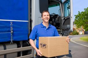 Truck driver standing near semi-truck holding cardboard boxの写真素材 [FYI02122203]