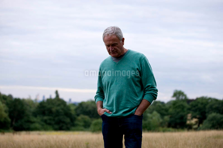A senior man standing in a field, looking downの写真素材 [FYI02122245]