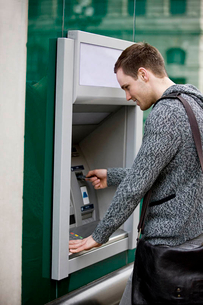 A young man using a cash machineの写真素材 [FYI02122271]