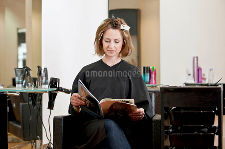 A female client reading a magazine whilst she has her hair coloured in a hairdressing salonの写真素材 [FYI02122281]
