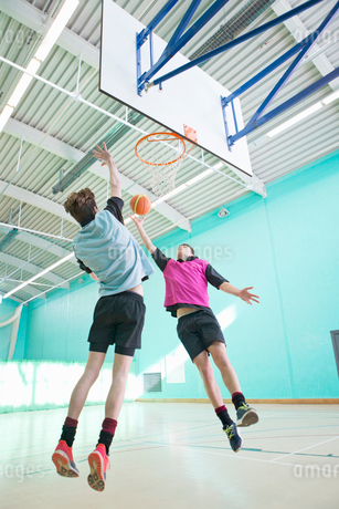 High school students playing basketball in gym classの写真素材 [FYI02122289]