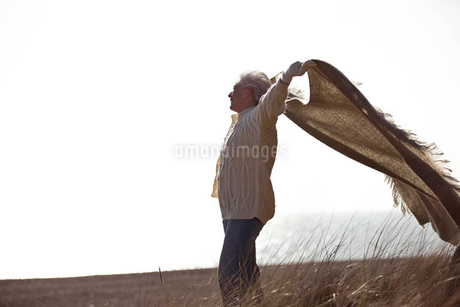A senior woman standing on the beach, holding a blanket into the windの写真素材 [FYI02122299]