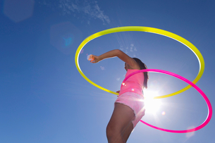 Girl spinning two plastic hoopsの写真素材 [FYI02122304]