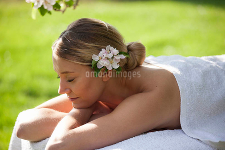 A young woman laying on a massage table under a tree in blossom, eyes closedの写真素材 [FYI02122308]