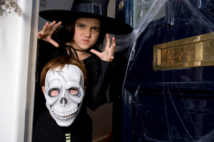 Young boy and girl at the front door, dressed up for Halloweenの写真素材 [FYI02122314]