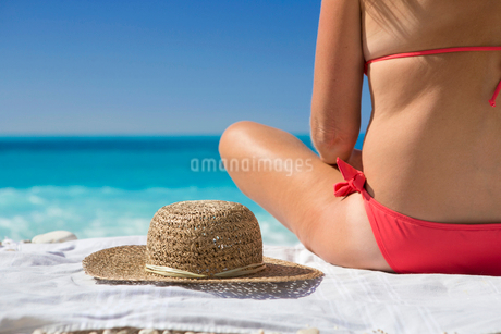 woman, sitting on towel with sun hat, on sunny beachの写真素材 [FYI02122319]