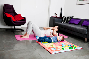 A mother and her baby son exercising at homeの写真素材 [FYI02122325]