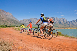 Family mountain biking in mountains by lakeの写真素材 [FYI02122326]