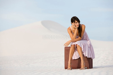 A young woman sitting on a suitcase in the desertの写真素材 [FYI02122343]