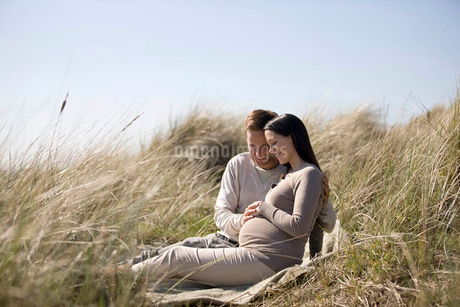 A pregnant woman and her partner sitting amongst the sand dunesの写真素材 [FYI02122367]